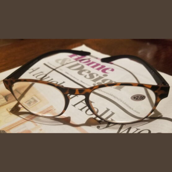 Brown reading glasses left on Irish Times